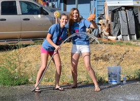 Two Carey cheerleaders holding a hose and water balloons at a station during the fun run.
