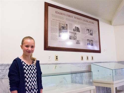 11-year-old Anna Wiese standing in front of an exhibit commemorating Idaho's first women legislators