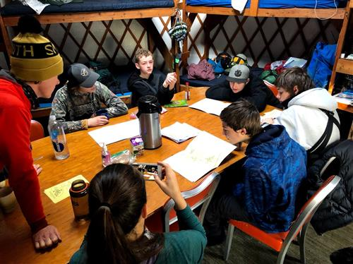 students in a yurt working together