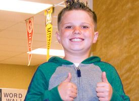 Hailey elementary student with two thumbs up outside of a classroom.