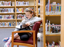 photo of student sitting in chair reading at the wood river middle school library