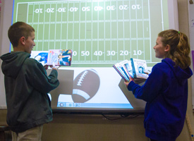 Two students comparing the length of books to a football field.