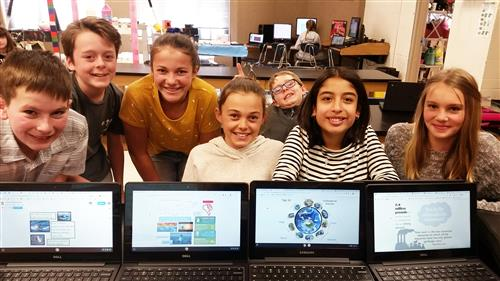 Students in front of computers with images fo earth day