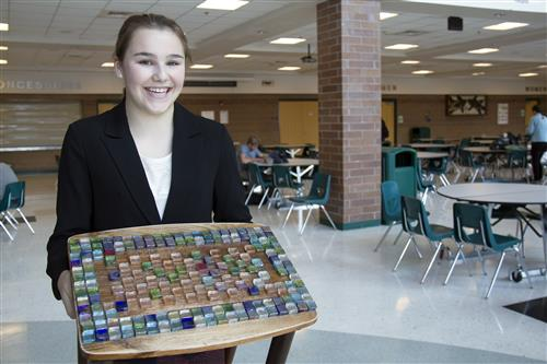Student holding mosaic coffee table