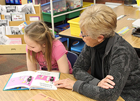 parent reading to student at school