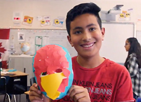 Student holding up a mask