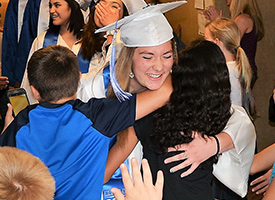 Carey graduate smiling and hugging elementary students.