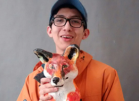 Wood River High School Student holding an orange ceramic fox