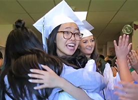 High School Graduates hugging elementary students.
