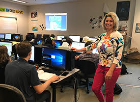 Becky Duncan standing in her classroom with students working on computers