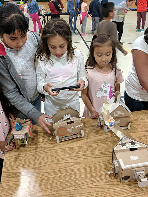 students using handheld computer to activate cardboard toys