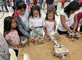 students using handheld computers to active cardboard toys