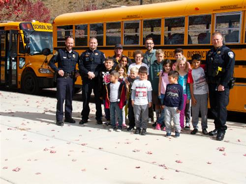 law enforcement with students in front of a bus