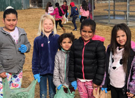 students holding plastic bags with garbage found on playground