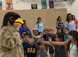 students gathered in the gym greeting Eagle mascot