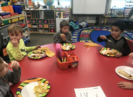 students eating at round red table in classroom