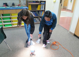 students testing solar car in classroom