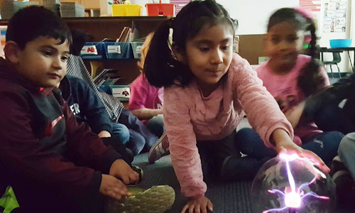 students touching a plasma globe