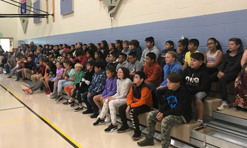 5th Grade students sitting on bleachers at 1st assembly