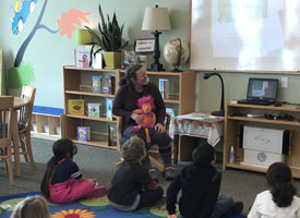 librarian reading Dr Seuss to students sitting on the floor rug