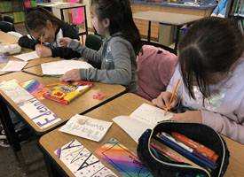 students writing thank you cards in classroom