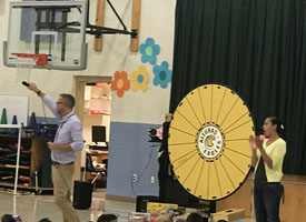 Principal addressing students and standing by prize wheel