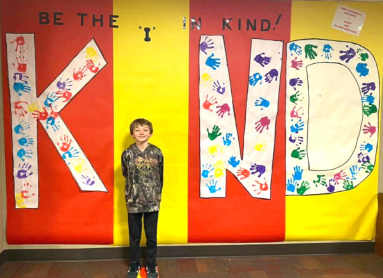 Student in front of Kindness Day Wall