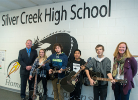 students holding new guitars